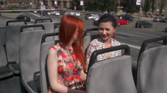 Young sexy women listening audiotape on an open top bus Stock Footage