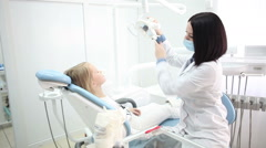 Young handsome dentist treats tooth girl child in dentistry. - stock footage