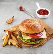 Cheeseburger and potato wedges - stock photo