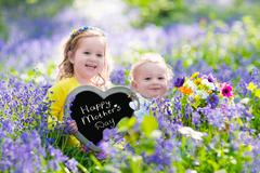 Kids with flowers and chalk board - stock photo