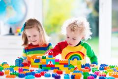 Kids playing with colorful plastic blocks - stock photo