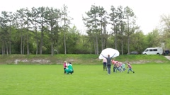 Tutors playing with children on a lawn Stock Footage