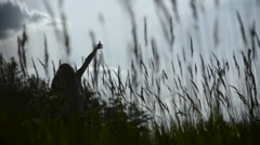 Silhouette of dancing girl in high grass - stock footage