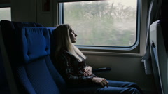 Woman in moving train feels pain in stomach Stock Footage