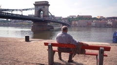 An Old man sitting alone on bench and looking at the river Stock Footage