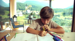 Child doing homework at home in the mountains getting tired dolly shot Stock Footage