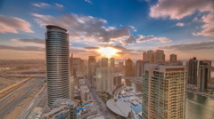 Modern skyscrapers and water channel with boats of Dubai Marina at sunset Stock Footage