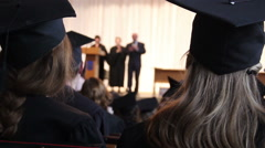 Many young guys listening to headmaster's speech at college graduation ceremony Stock Footage