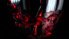 Filling wine glass with red wine super slow motion macro shot, black background Stock Footage