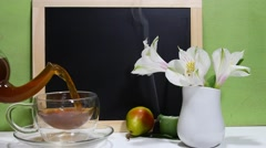 A glass tea kettle pouring black tea in a transparent tea cup. - stock footage
