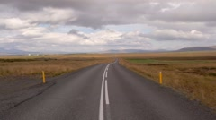 Icelandic road is across a fields in cloudy weather Stock Footage