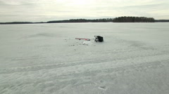 Overflight shot of an ice fishing hole with fish and fishing equipment Stock Footage