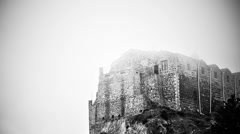 Black and white mysterious haunted castle standing on foggy top of mountain Stock Footage