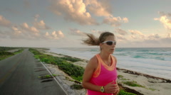 Female runner in sport dress running at the sea slow motion Stock Footage