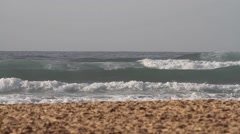 Waves rolling towards the sand beach on a sunny day - stock footage