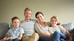 Portrait of happy family sitting in sofa Stock Footage