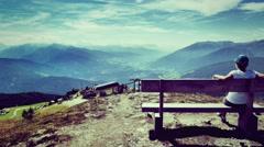 Woman on bench enjoys the mountains Stock Footage