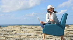 Woman using laptop by the sea, sit in armchair - stock footage