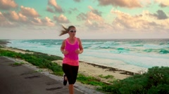 Female runner in sport dress working out at the sea slow motion Stock Footage