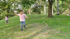 Little sibling boy playing plane paper in the park - stock footage