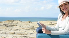 Woman reading book in armchair by the sea - stock footage