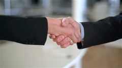 Two co-workers (woman and man) do an handshake, he shows their hand first. - stock footage