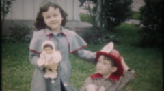 Cute brother and sister play together in frontyard -3238 vintage film home movie Stock Footage