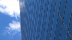 Skyscraper building all-glass elevation with reflection of sky and cloud drift. - stock footage