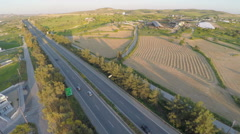 Aerial shot of many trees, harvested farming fields, green hills along highway Arkistovideo