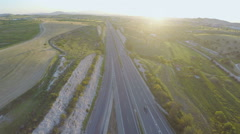 Vehicles moving on interstate highway. Beautiful sunset on horizon. Aerial shot Arkistovideo
