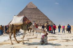 Local man renting camel to tourist in front of the Great Pyramid of Giza. - stock photo