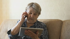 Grandma talking on a cell phone with a friend Stock Footage