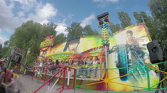 Slow-mo of people having fun at amusement park, riding wildly spinning carousel - stock footage