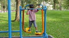 Asian kid boy exercise with walking equipment at outdoor fitness in public park Stock Footage