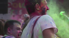 Many young guys dancing, having fun at Holi Fest. Colorful paint spraying in air Stock Footage