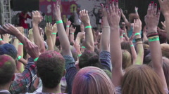 Man throwing paint powder in crowd from stage, people enjoying fest, hands up Stock Footage