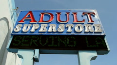 Adult store sign on blue sky in sunny day Stock Footage