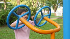Asian kid boy exercise with wheel equipment at outdoor fitness in public park - stock footage