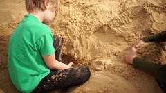 Brothers burrowing hole in sand in Oleshky sands.Ukraine. Slow motion Stock Footage