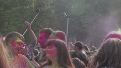 Young guys covered in color powder dancing to music, having fun, enjoying event Stock Footage