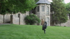 Teen Girl Runs Across Field to Stone Castle Tower Stock Footage
