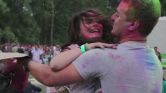 Girl jumping on guy, couple hugging, you people have fun at outdoor festival - stock footage