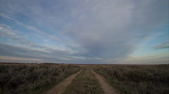 Timelapse of morning light rising over two track dirt road in sagebrush prairie - stock footage