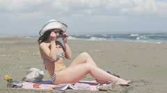 Attractive young woman suntanning on seaside beach. Stormy sea, windy weather Stock Footage