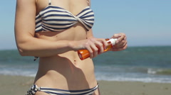 Slim female with hot body applying sunscreen oil, rubbing belly and hips gently Stock Footage