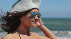 Professional female model posing for photo shoot on sea beach, smiling at camera - stock footage