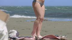 Woman on beach applying SPF sunblock spray on legs to protect skin from sunburns - stock footage
