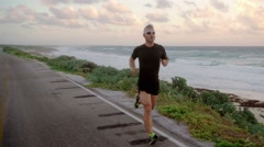 Male runner in sport dress working out at the sea Stock Footage