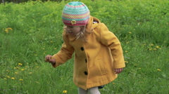 A three years old girl playing and plucking flowers in a park. Slowly Stock Footage