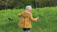 A three years old girl playing and holding flowers in a park. Slowly Stock Footage